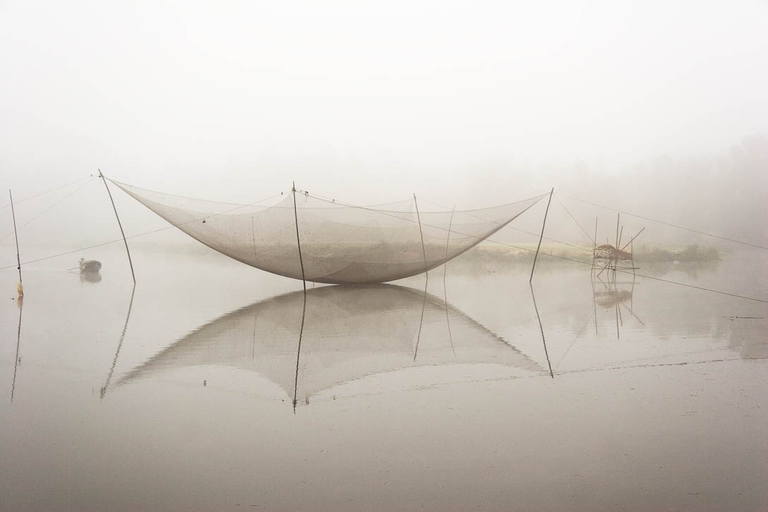 Fishing net on a river between My Son and Hoi An, Vietnam, In the early morning mist with a fishing boat approaching from the left. This photo just won an honorable mention in the International Photo Awards (IPA) 2010 competition. Photo by Jay Graham