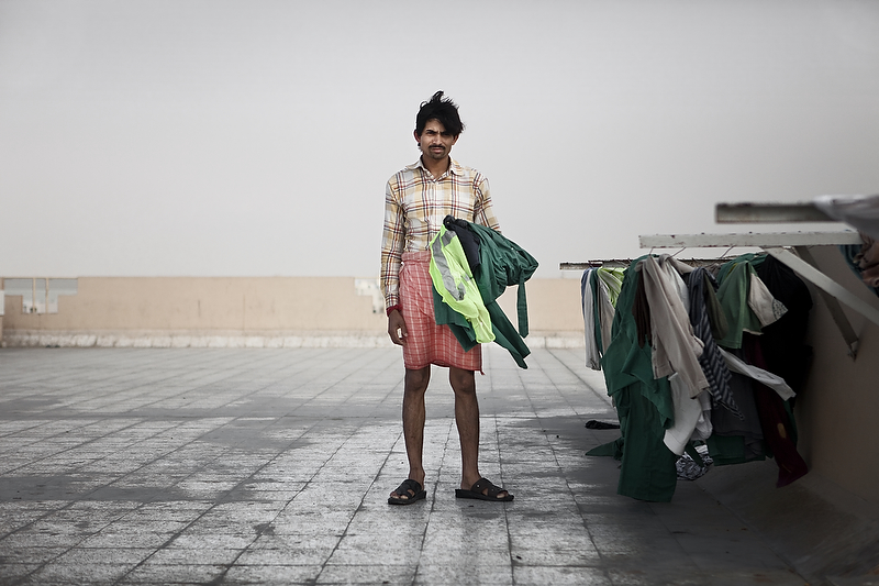 Moona Singh, an Indian laborer, picks up his clothes from a laundry line on the roof of a building at ICAD, a labor camp outside of Abu Dhabi. This is one of the few moments he has to himself throughout the day.