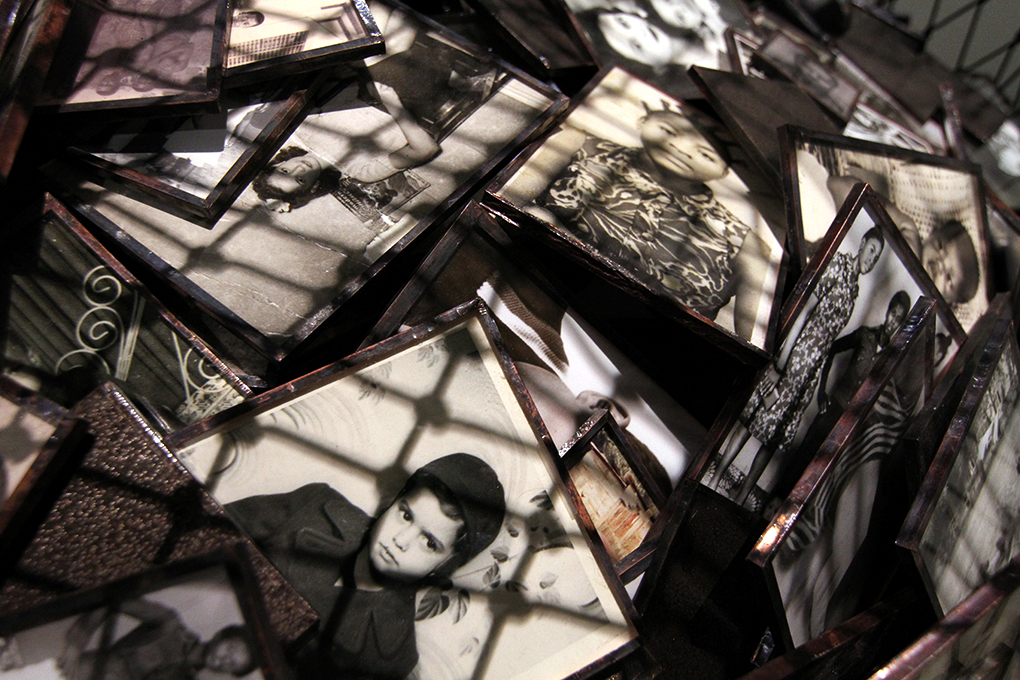 This sculpture considers photography's role in the creation of family narratives. Hanging from the ceiling in a giant net are the contents of family photo albums, owned by the parents of the artist and her husband before they were born. Thousands of hand-framed images bury each other, emphasizing the impossibility of understanding one's history, and posing questions about photography's role in what is remembered and forgotten.