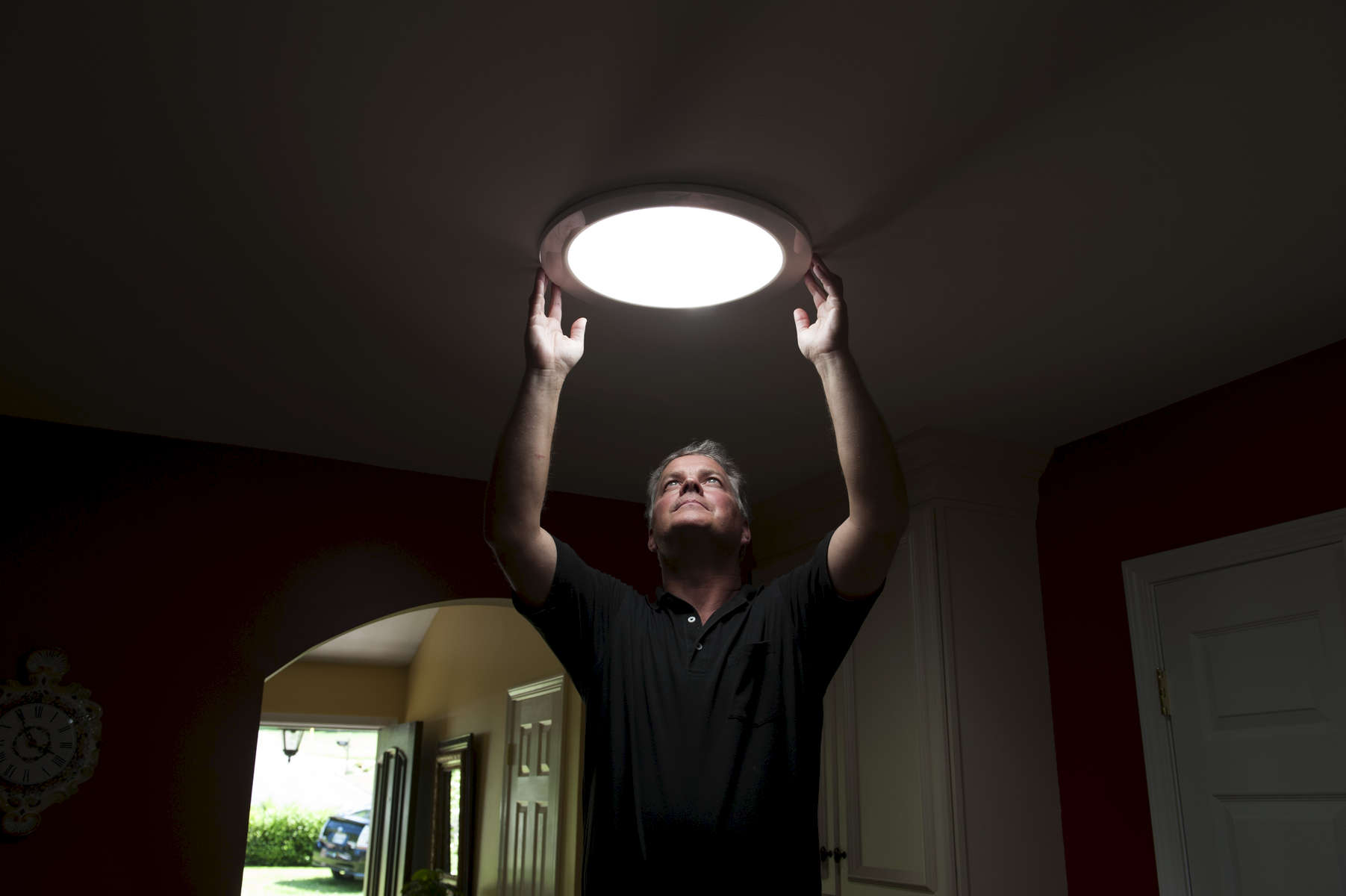 An advocate of energy efficiency installs skylight in his home to cut down on electricity use.