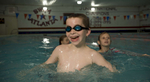 A young boy on the autism spectrum enjoys swimming lessons at a community pool.