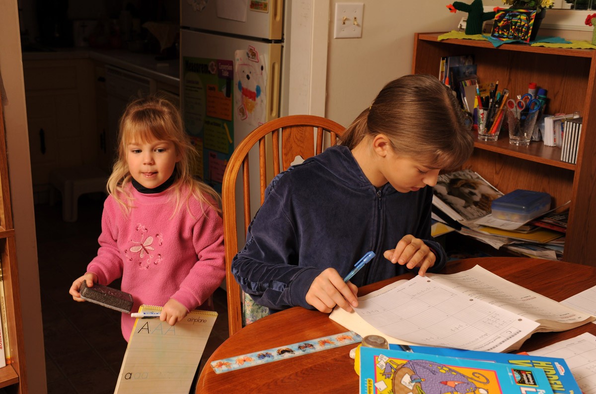 Four-year-old Demaris gerts ready to study her letters while sister Lydia , 11, works on math problems. The children work on academics at least five hours a day.