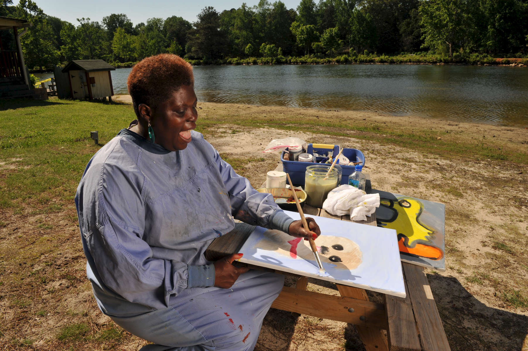 "Decatur, GA – Ten years after the U.S. Supreme Court's landmark ""Olmstead"" decision made it possible for mentally disabled persons to live within their communities rather than state mental hospitals, 41-year-old LOIS CURTIS is all smiles, loving her life beyond locked doors and high fences.A self-taught artist, Curtis spent much of her life in various mental institutions. Following denial of numerous requests to live in her community, she initiated a lawsuit against the state of Georgia. In July, 1999 the U.S. Supreme Court ruled that 'unnecessary institutionalization' amounted to segregation and violated individuals' civil rights. Her case established a national mandate to free tens of thousands of people with disabilities from institutionalization. Today, Ms. Curtis receives community-based support and enjoys life outside the confines of institutional living. Her artistic talent and passion for creativity have motivated her to make art and advocacy her life's work. Her artwork, typically done in pastels and acrylics, are heartfelt, bold expressions of how deeply she values personal relationships.  They are mainly portraits, capturing intense emotions with simple lines and bold colors. ""I feel good about myself. Sometimes I put my mind on the earth and go to the future where my art pictures are on the wall. People would love to see my pretty art pictures because they will take them to heaven and hug them forever,"" says Ms. Curtis. Her supporters have arranged for dozens of art shows in the Atlanta area, and she is now an invited speaker to conferences nationwide. Pictured: Lois paints wildlife at Pine Lake, an artist community near Atlanta where Lois dreams of living."