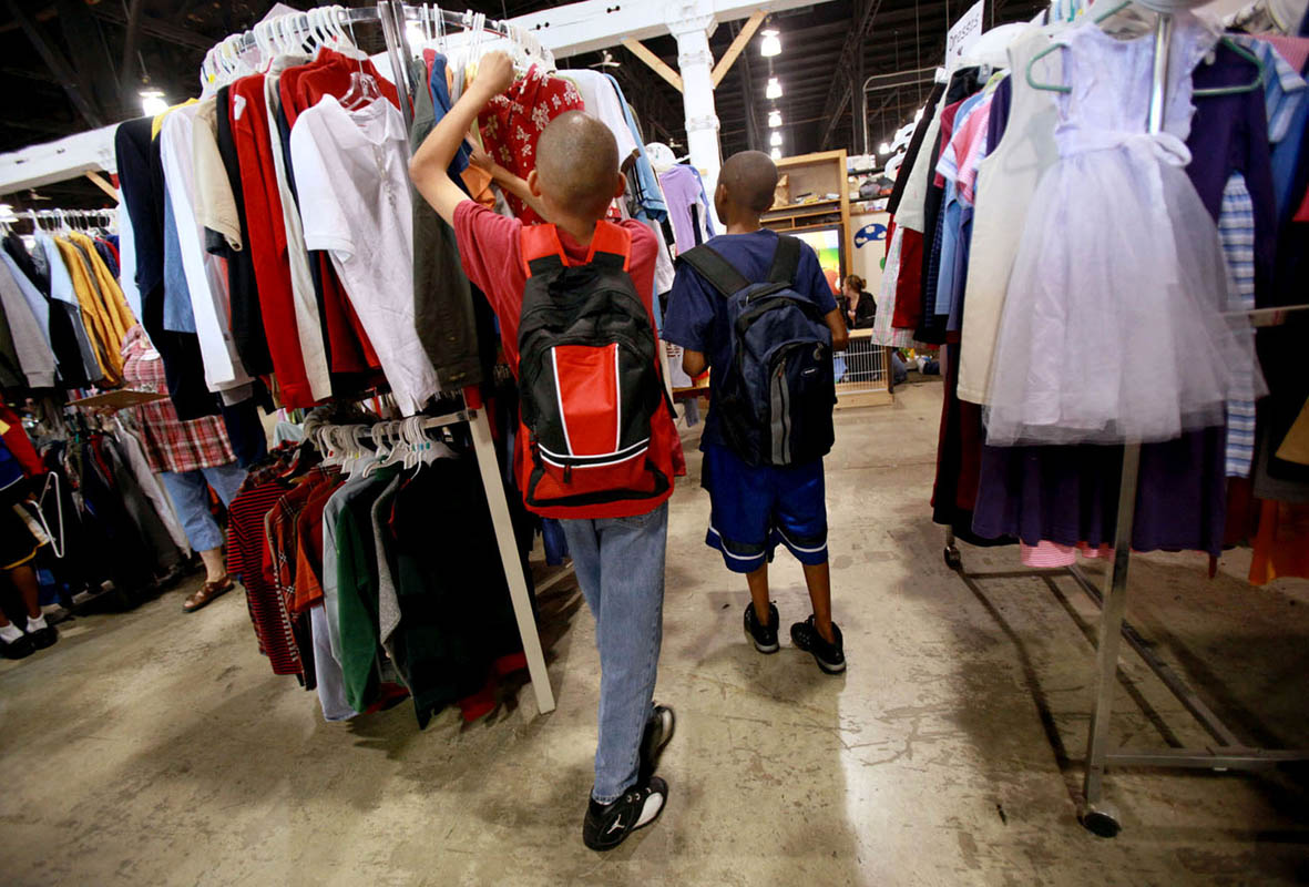 Outfitted with new backpacks, two brothers shop for school clothes as they attend the Back to School Boost. Many charity organizations like Lutheran Social Services who sponsored the event, have seen an increase in families needing their help. Area businesses like Kohls donate clothing, school supplies and other items for the program.
