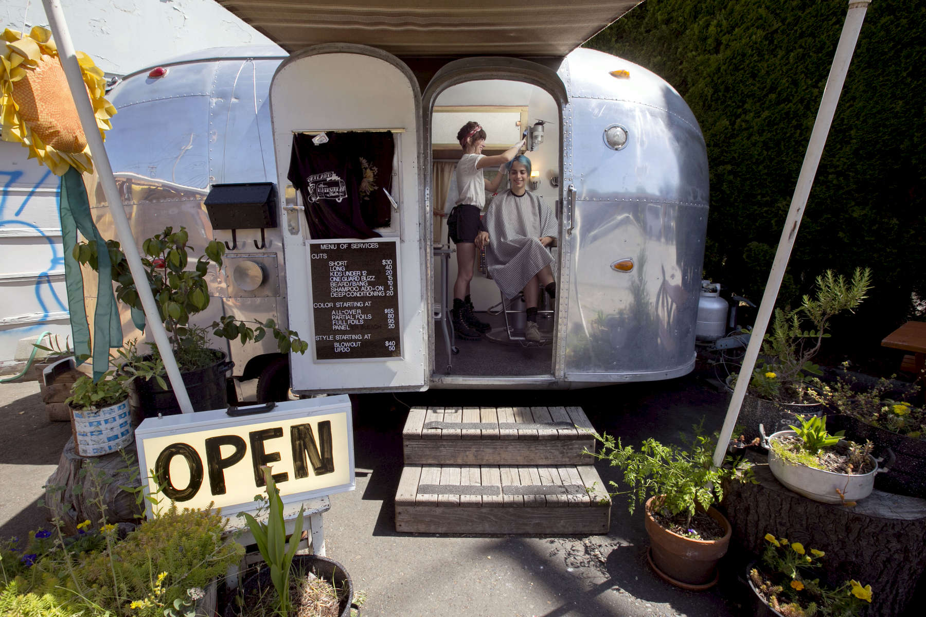 Anna Gale (left) works on customer Anja Memovic's hair at The Hairstream Trailer, a single-seat hair salon is housed in a 16-foot Airstream Bambi trailer in Portland.