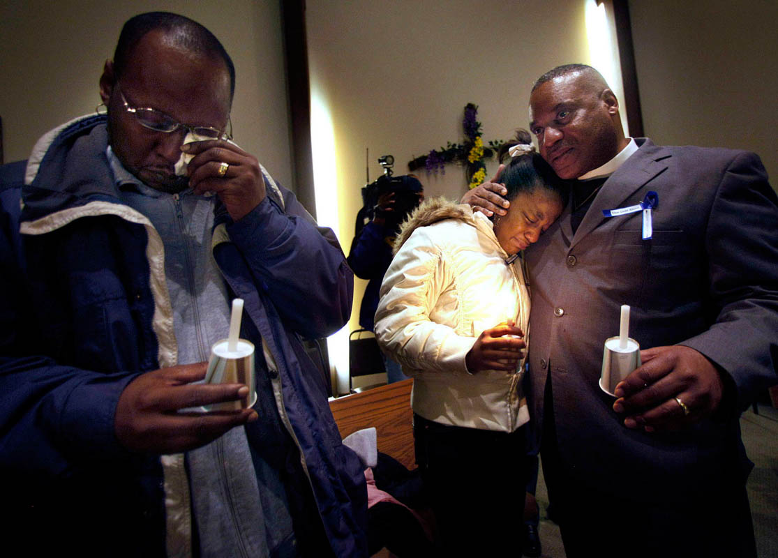 Kenny McClellan, grandfather Christopher Thomas, Jr., (left) wipes his tears as his daughter Shantrina Freeman, 12, (center) is comforted by minister Gregory Lewis, (right) following a candlelight vigil held for Christopher Thomas, Jr. Signs of violent child abuse were not recognized by the child's caseworker, and Thomas died of injuries after a severe beating.