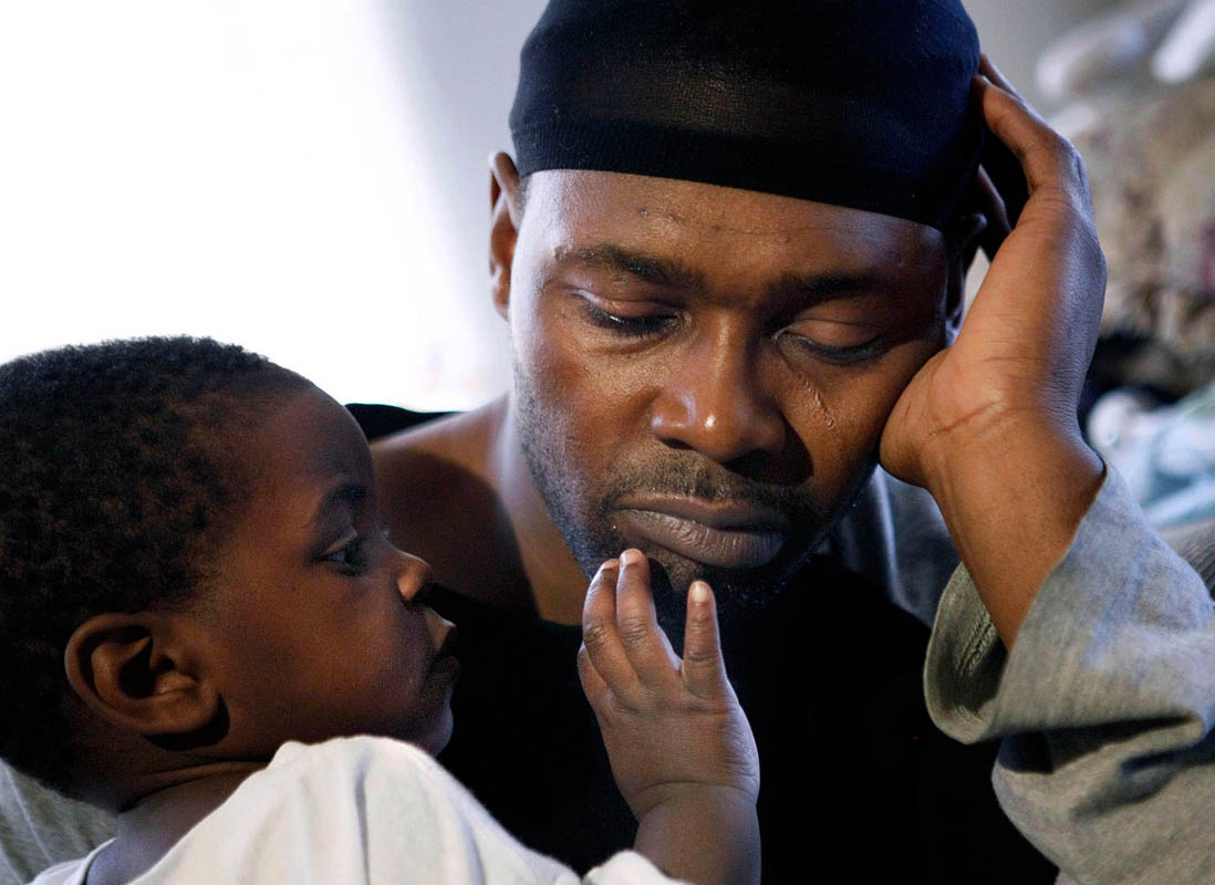 Cedric Buchanan (right) is comforted by his son Branden, 1, as Buchanan deals with news of his six-day-old daughter's death. The baby died while sleeping on the couch with her intoxicated mother, Rose Prescott. This is Prescott's second child in 13 months that has died in the same manner. After the first child died, the mother was investigated for child endangerment by the bureau. They knew she had another child but did not return to ensure it's safety.