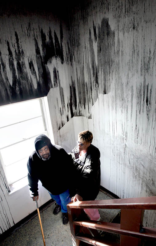 London Scott and Sandra Scott stand in the smoke damaged hallway outside of their Milwaukee apartment, February 20, 2006. A fire in the neighboring apartment on two months previous left extreme smoke and water damage, as well as broken windows, none of which has been repaired by the landlord who was on the Milwaukee County Board of Supervisors. They are the only ones living in the apartment complex and due to limited finances, are unable to leave.