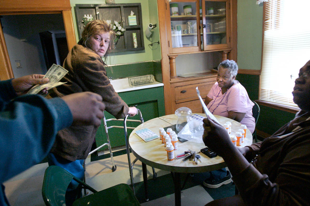 Landlord Dawn Powell, far left, is handed money to buy supplies for tenants at their Milwaukee home, January 31, 2006. Both Susan, center left, and Bessie, right, were patients at the mental hospital as a result of their chronic mental illness. Although both women have caseworkers, their lifes really are in the hands of the landlord, who is supposed to provide shelter and food.