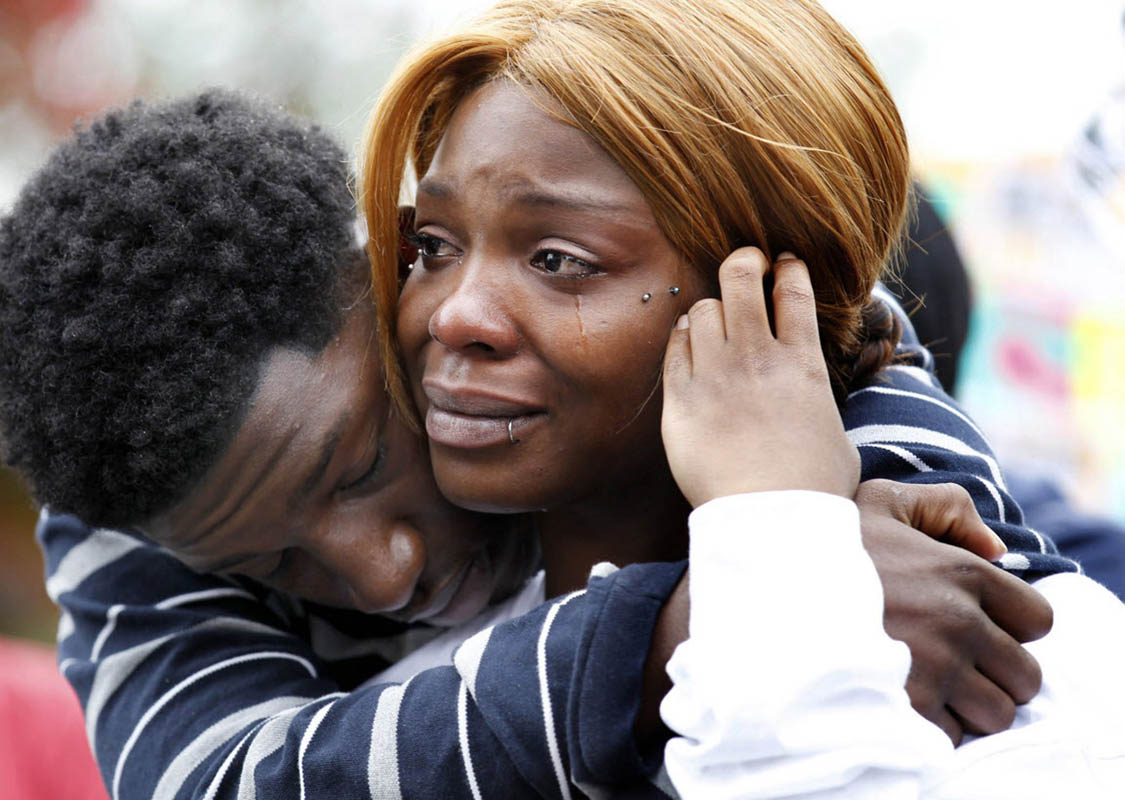Jalil Pugh, 16, (left) and Taquila Pugh, 19, comfort each other as they gather with marchers on Martin Luther King Jr Drive on Milwaukee to protest the death of their brother Derek Williams. Williams died in the back of a police car last year. About 100 people marched downtown and ended at the Milwaukee Police Headquarters, demanding the police chief step down and justice for Williams.