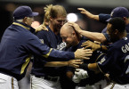 Casey McGehee is surrounded with teammates, including coach Ken Macha (left) after McGehee came up with a hit in the bottom of the 9th inning, on a full count, that scored two runs to give the Brewers the win over the Cubs.