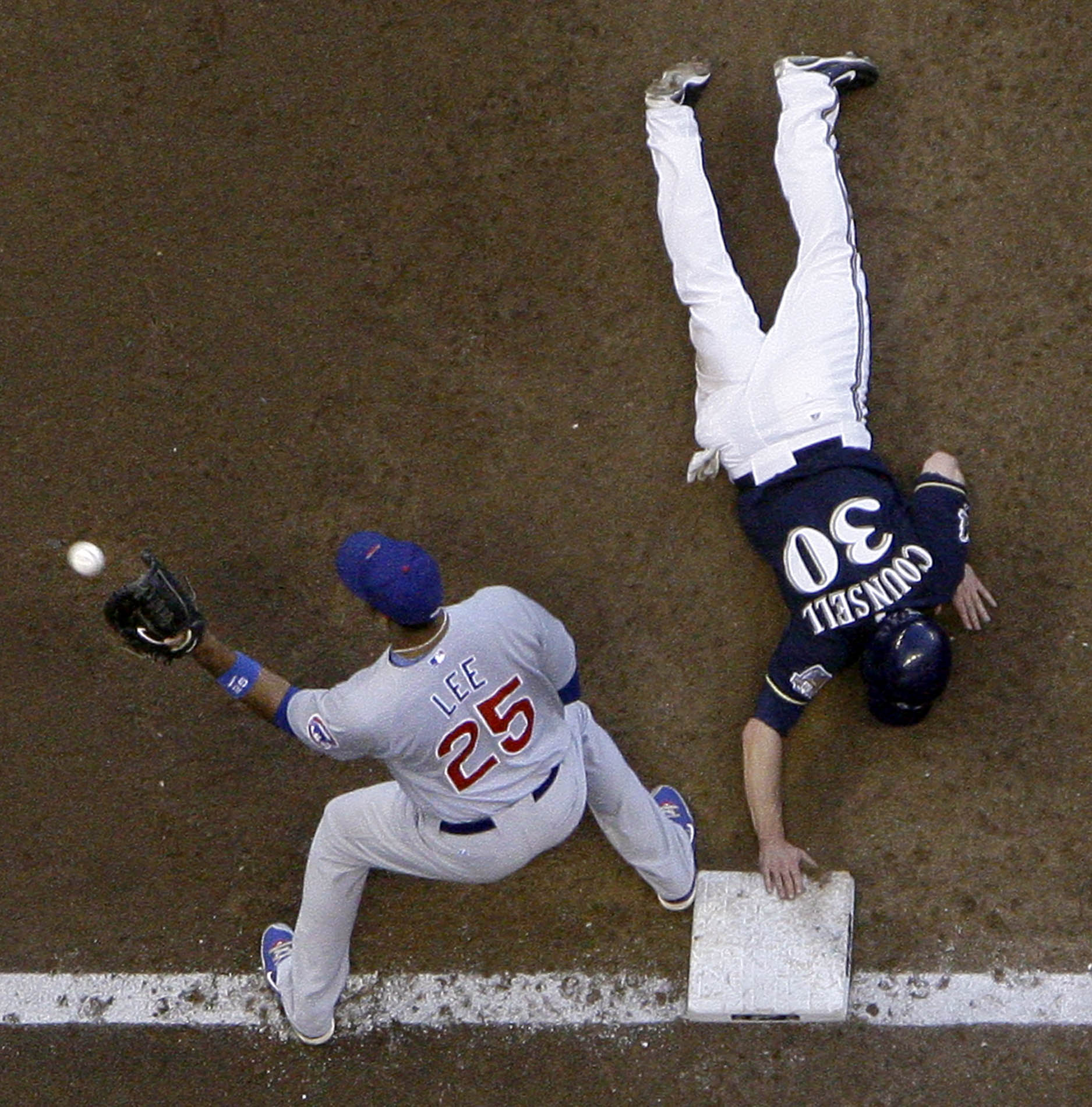 Craig Counsell dives back to first to beat the tag in the third inning of the Cubs vs. Brewers series at Miller Park