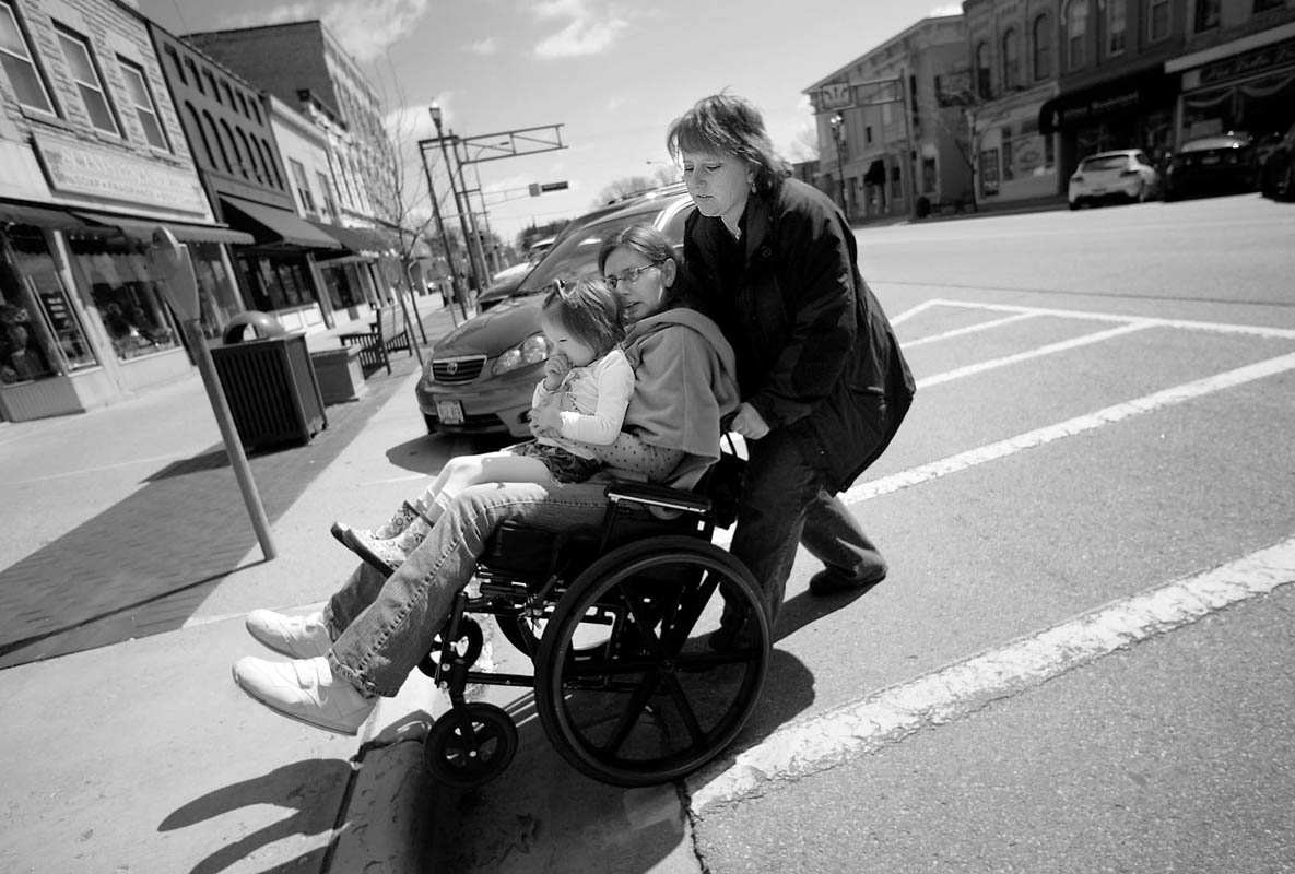 Juli Henrie, right, wheels her sister Courtney Johnson-Atherden, center, over a curb in Lake Geneva, April 5, 2007. Juli's daughter Brinn, 4, rides on her aunt's lap. Juli brought her sister home to live with her and says although Courtney needs a lot of care, the decision was easy. Nearly all of Courtney's memory has been erased, but one person she did not forget was her favorite sister, Juli.
