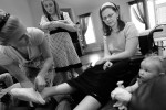 Courtney is surrounded by her neices Brooke Johnson, left, Brittney Henrie, 12, center left, and Kayla Dawn Johnson, 2, right, as they try to make her comfortable by putting warm socks on her feet. Courtney can speak, but is often confused by directions and has difficulty finding the right words to describe what she wants.