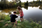 Izzy and older sister Angeliah hold hands while exploring a pond in Winnequah Park in Monona in August. Izzy's sisters had difficulty at first, calling Izzy 'she,' and then switching to 'he.'