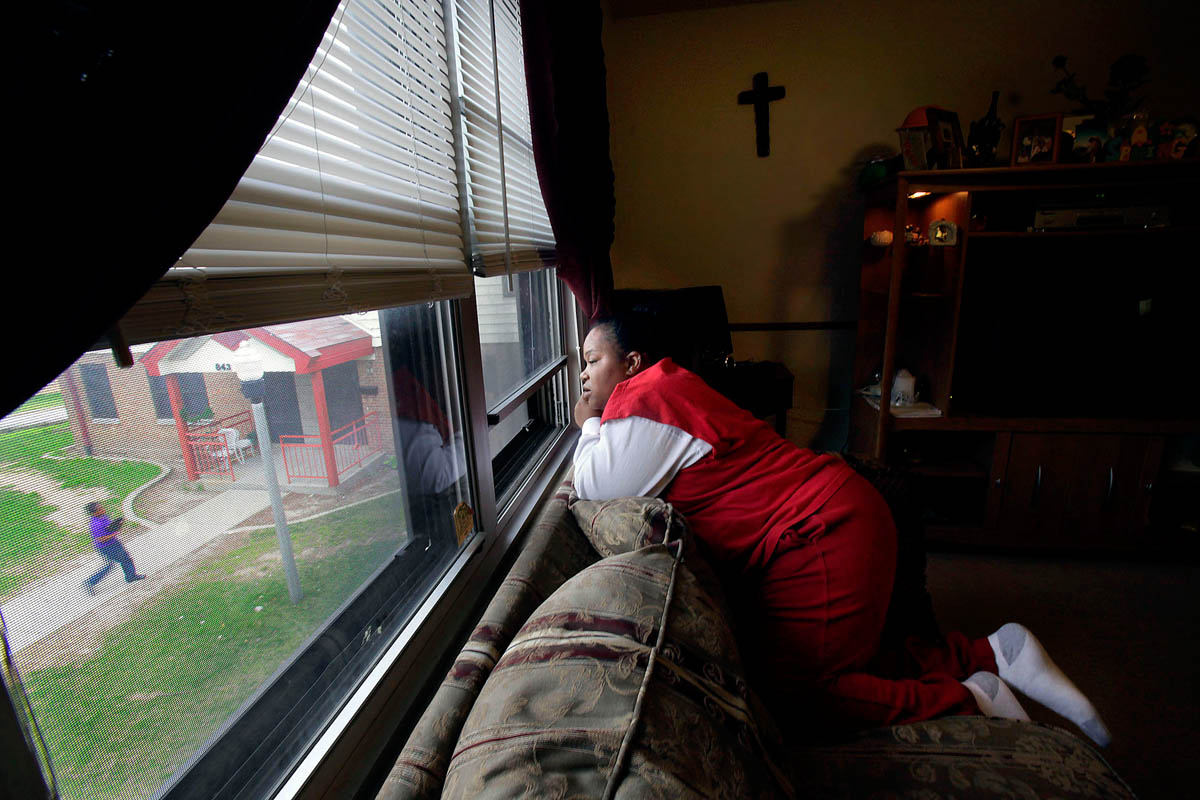 Brandy looks out the window at her children Tae, 12, and Shakiem, 10, who play in the courtyard below. The boys were each removed from Brandy's care shortly after their births, and have spent the majority of their lives in foster homes. Brandy regained custody of them twice before, but lost it shortly thereafter when she returned to drugs. She has now been clean for months and is working towards reunifying with the boys for a third time.