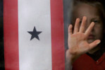 Dakota Lane, 6, pauses during his play near a flag hung at his Manawa home. The flag is a symbol that a soldier is away from home engaged in military service. Dakota's father, Allen, has served 14-months of duty overseas and nearly to the day he left, Dakota began having problems. Regular bedwetting, inappropriate behavior, and aggression were all new behaviors for this typically quiet child.