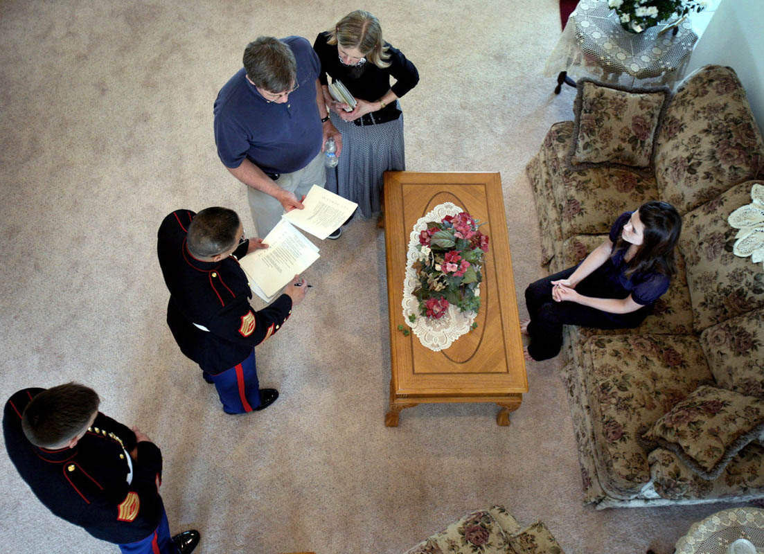 Kristen sits on the couch as Marines give their condolences and discuss arrangements with the family, including his parents Lennie and Susan Nelson, left. The family still does not yet know exactly how Ricky died, and await the return of his body.