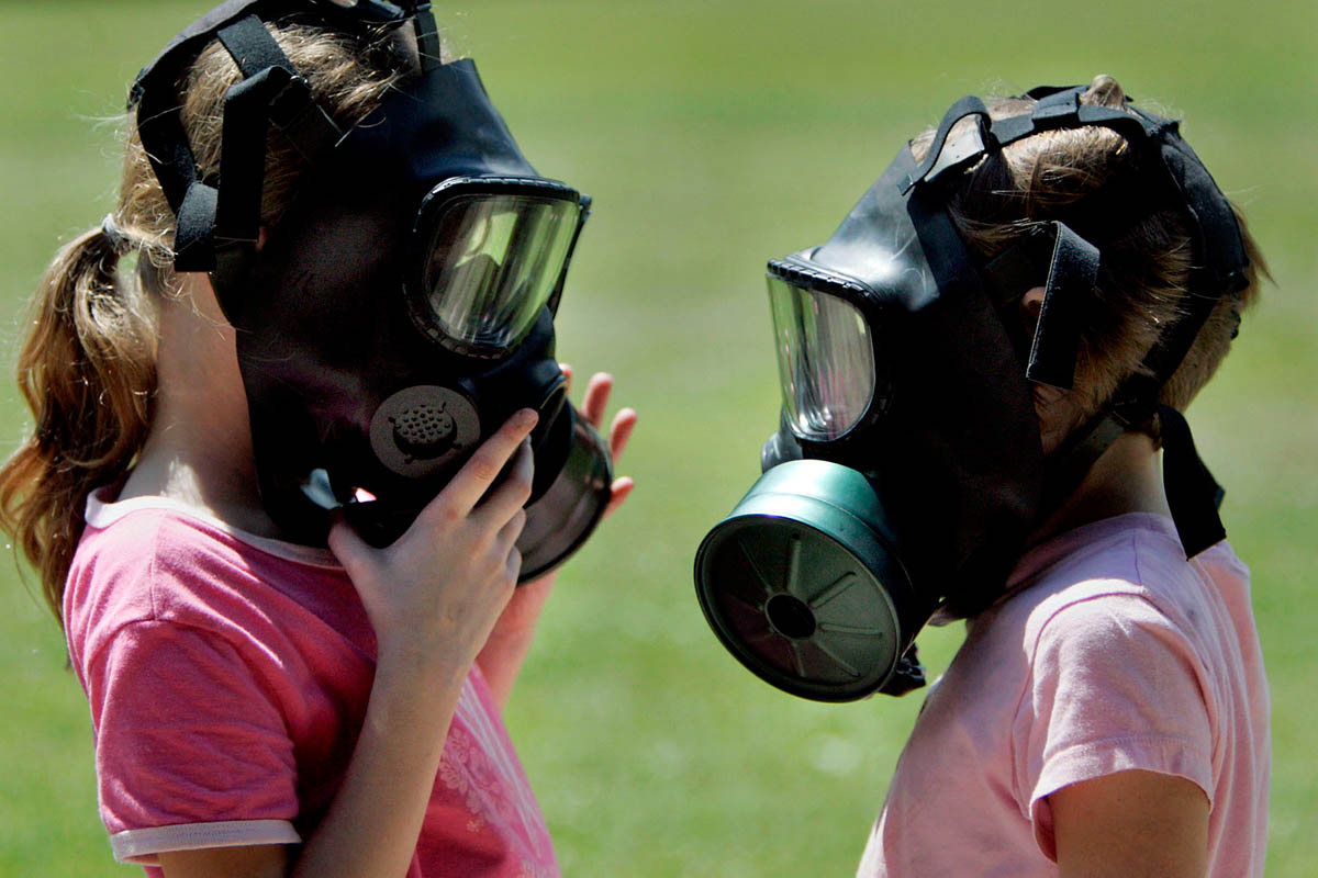 Two children chat while wearing gas masks During Operation Purple camp. The camp was designed to give military children a place to interact with one another and discuss having parents who are in Iraq. At this event, kids could try on gas masks, helmets, flak jackets, and other equipment used by members of the military.