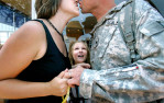 Saharra Lane, 9, of Manawa, watches eagerly as her parents kiss upon the return of her father, Allen Lane, from Iraq. Allen served with the Army National Guard's 1st Battalion, 121st Field Artillery and was deployed for 14-months. A soldier's return from war doesn't ensure the problems are easily resolved. They and their children aren't always aware just how much the war has rewired their relationships. It is not yet known what long term effects, if any, these children will deal with after their parents return, but it is agreed that not enough is being done to support them.