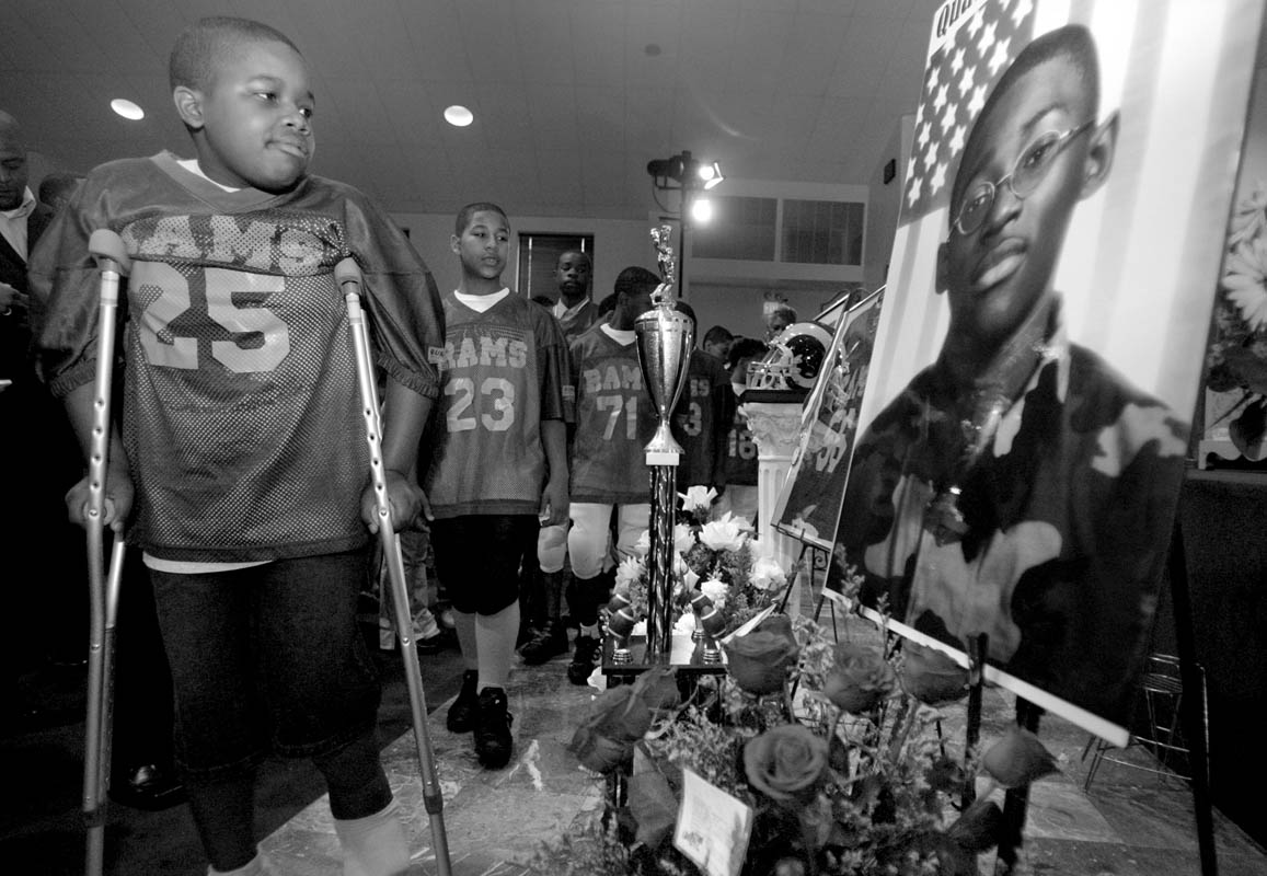 Members of the Neighborhood Center Sports League Mighty Rams team file past Quadrevion's photos at the start of his funeral services. Quadrevion played on the team for three years.