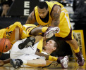 UW-Milwaukee Panther Paige Paulsen, center, is caught in a tangle of legs and arms as he scrabbles for a loose ball against Central Michigan's Jeremy Allen, far left, and Nate Minnoy, right, during Wednesday night's game at the U.S. Cellular Arena.