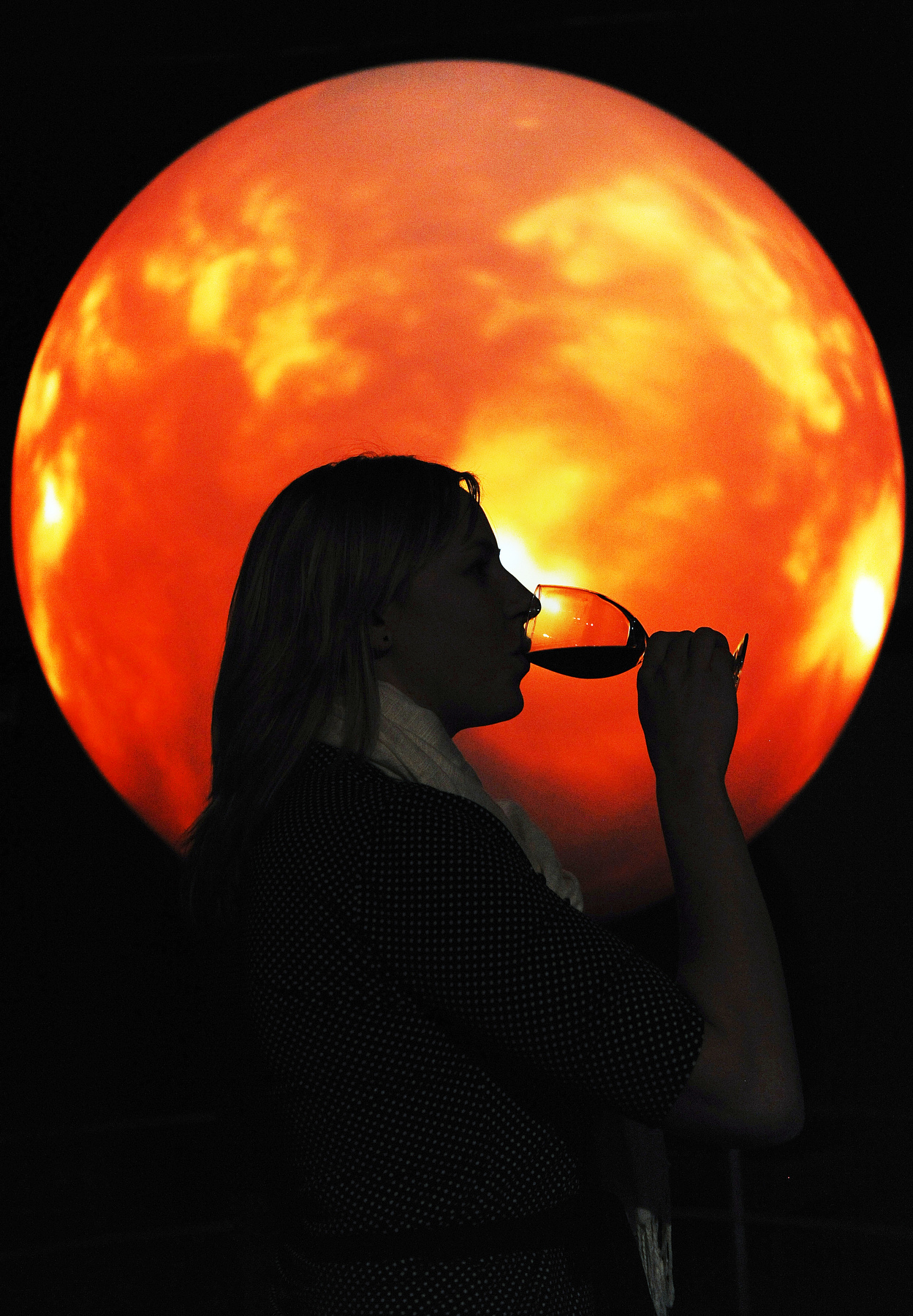 A woman drinks a glass of wine during Science Lounge at the Denver Museum of Nature & Science in Denver, Colorado.