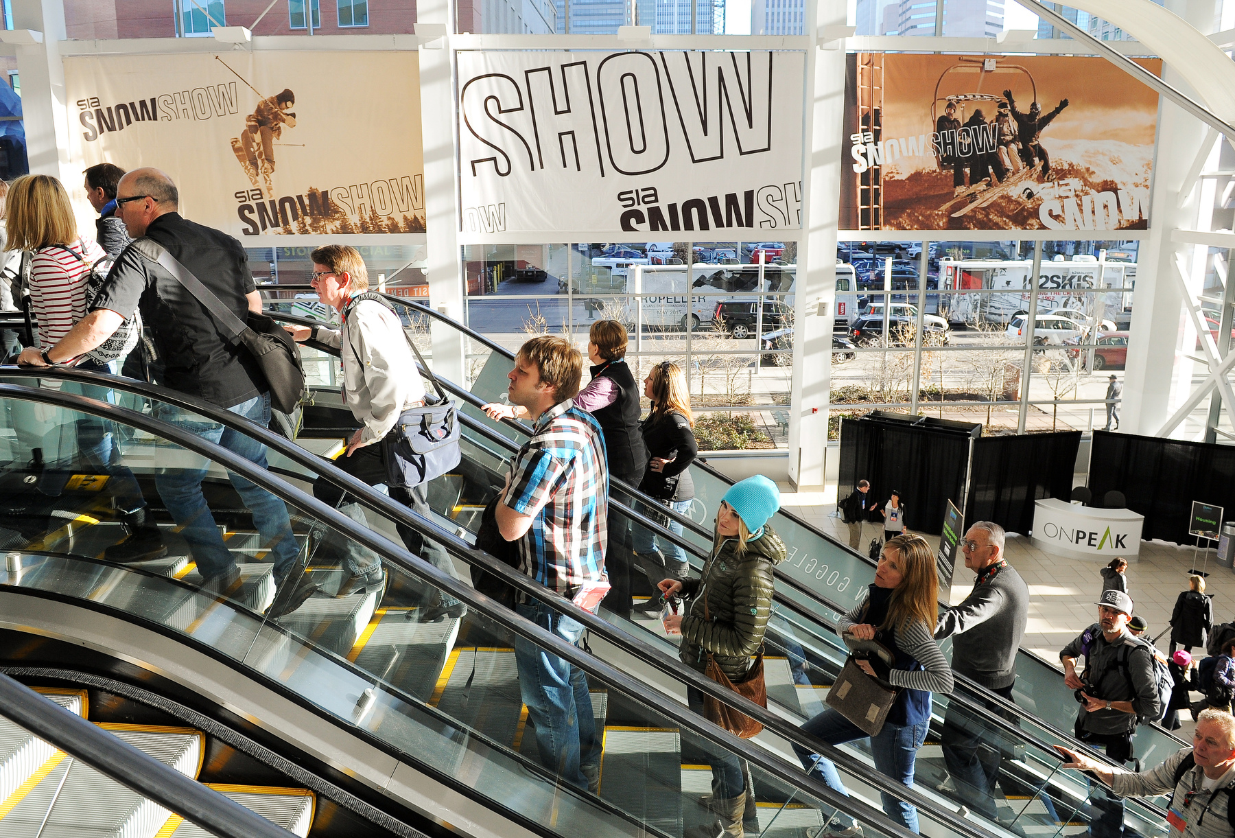 SIA Snow Show attendees ride the escalator to the floor show at the Colorado Convention Center.