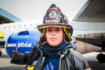Boston, MA., July 24, 2013: Fire fighter Joanna Westland, 23, performs a drill on a Jet Blue jet as part of a training exercise. In some cases, fire fighters will board a plane if there is a report of smoke in the cabin and evacuate passengers via the portable stairs instead of the inflatable slides which can cause injuries. Boston has one of the best airline fighting fighting crews in the nation. Photograph by Evan McGlinn for The New York Times.