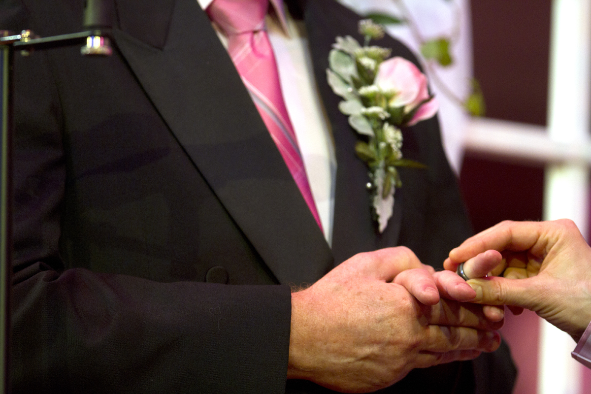Neil Hoyt (right) places a ring on Donald Jenny's finger during their wedding celebration at Benaroya Hall during the Seattle Men's Chorus Holiday Concert in Seattle, Wash., on December 9, 2012. Both from Bellevue, Wash., they have been partners for 23 years.  {quote}It's overwhelming.{quote} said Hoyt {quote}It's the biggest and best wedding party I can ever imagine.{quote}   (© Karen Ducey 2012)