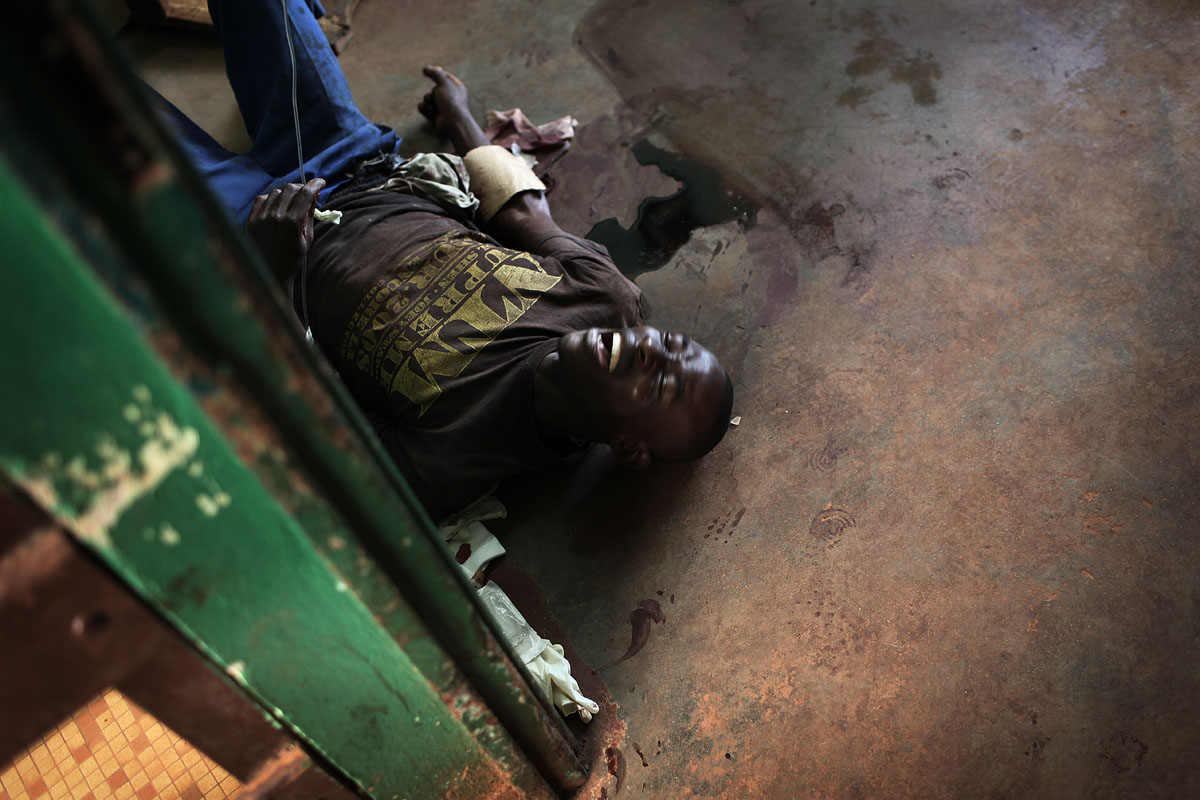 A wounded man shout as he is waiting for treatment at the hopital communautaire in Bangui.