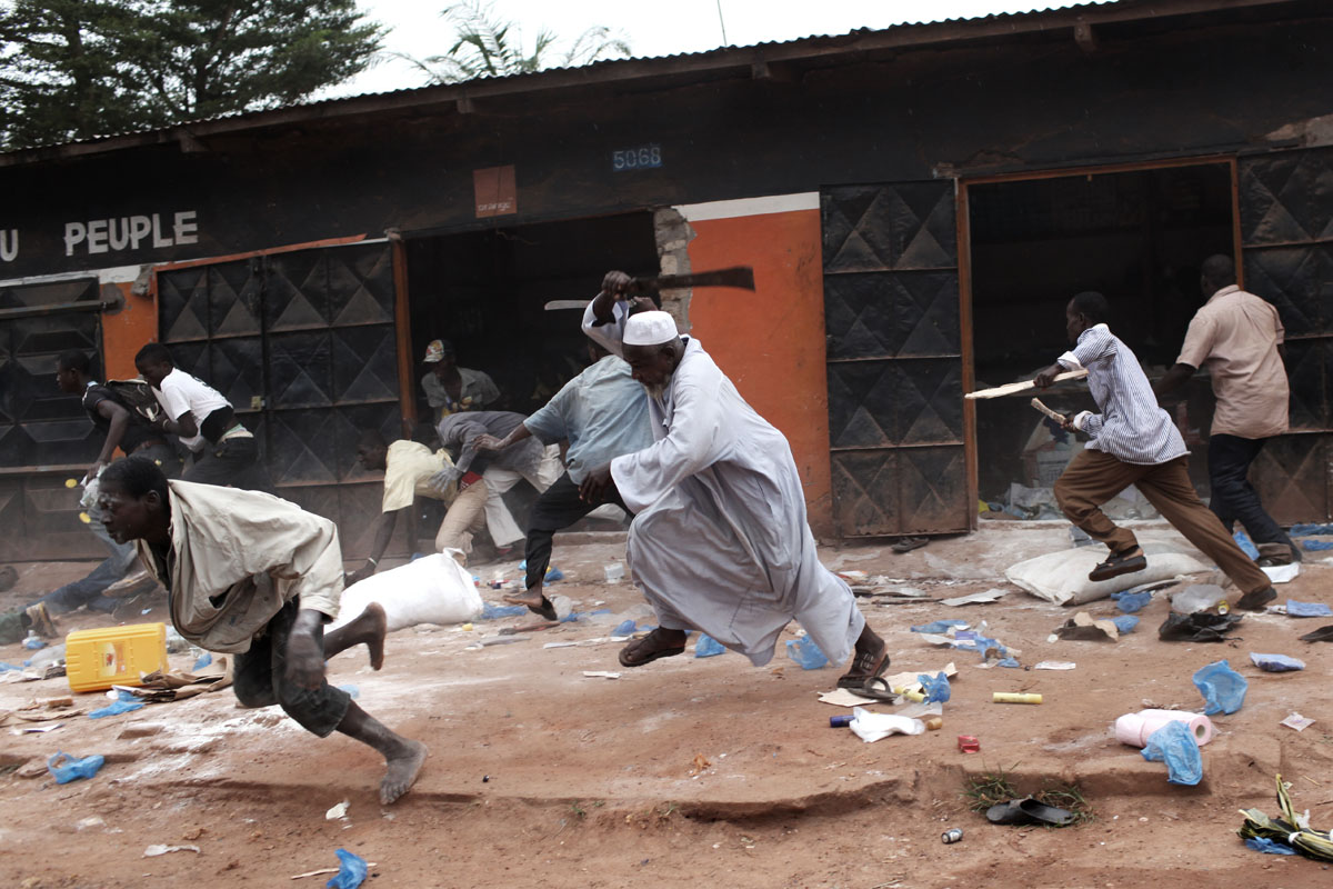 A muslim man,owner of a shop that has been looted by christians pepole is running after the looters with a machete and some friends of him.