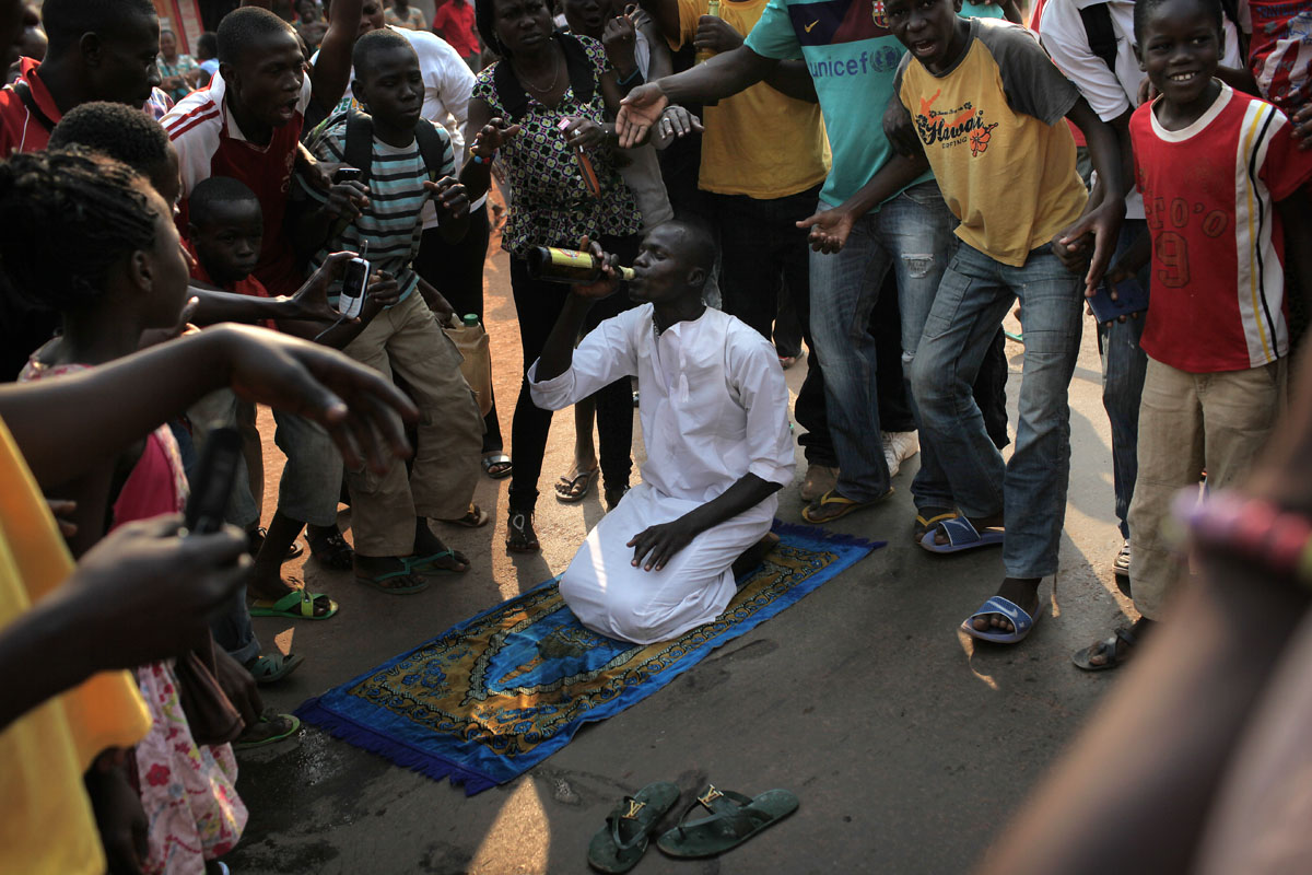 young Christians celebrate the departure of President Djotodia while drinking beers and desecrating muslim objects.