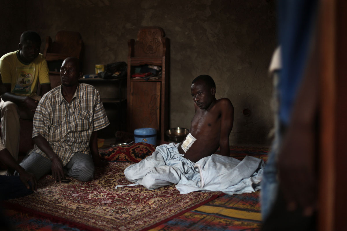A muslim man stays at home after being wounded by christians milicia outside his neighborhood.