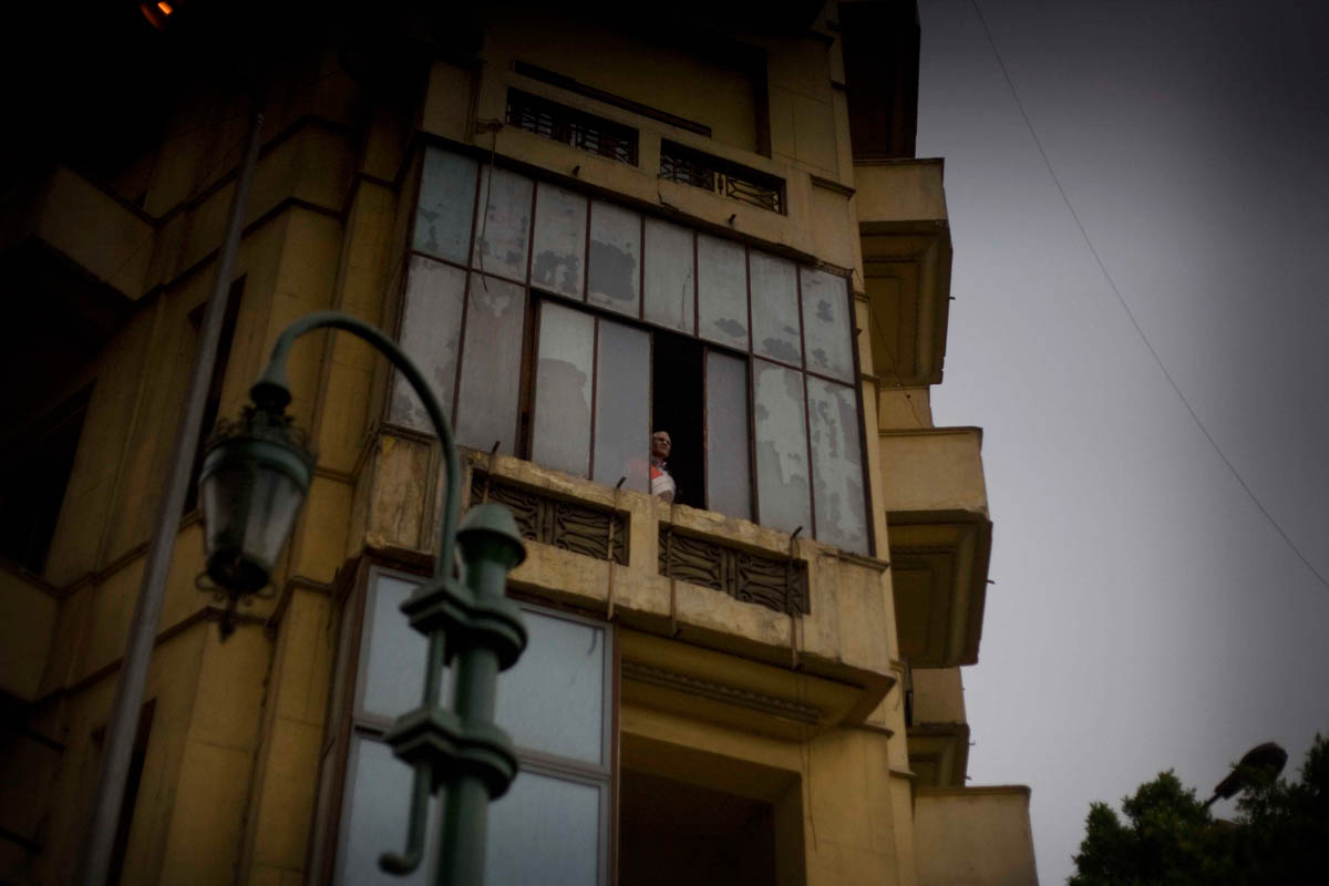 An egyptian man looks at the protests on tahrir square from his window.