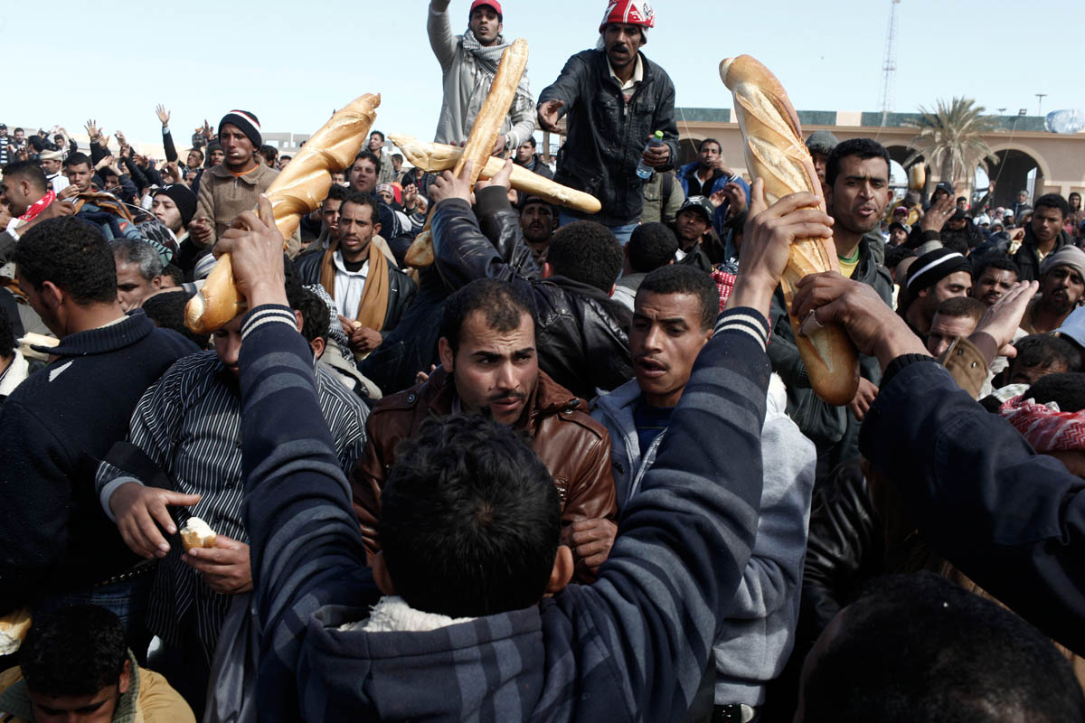 Food distribution and mess happen to Egyptian men who were working in Libya carry their belongings after they fled the country at the Tunisia-Libyan border, near the town of Ben Guerdane,Tunisia.
