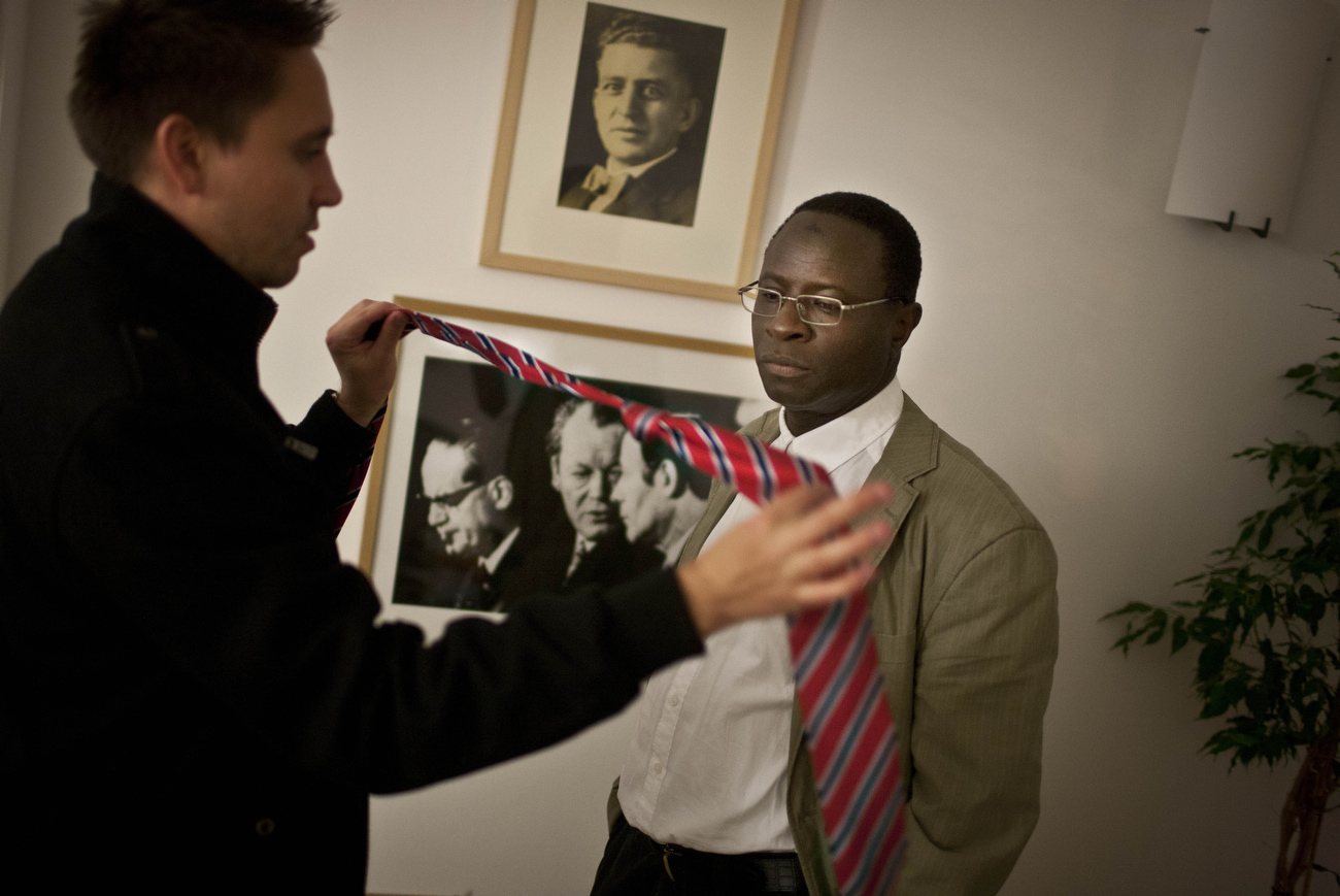 An aide hands a tie to Karambe Diaby during a dressing session in preparations for a pending first trip as an elected member of Parliament to Berlin. Senegales born Diaby, a PhD in chemistry, canvassed the former hub for East Germany's chemical industry to become the first black member of the Bundestag in German history.