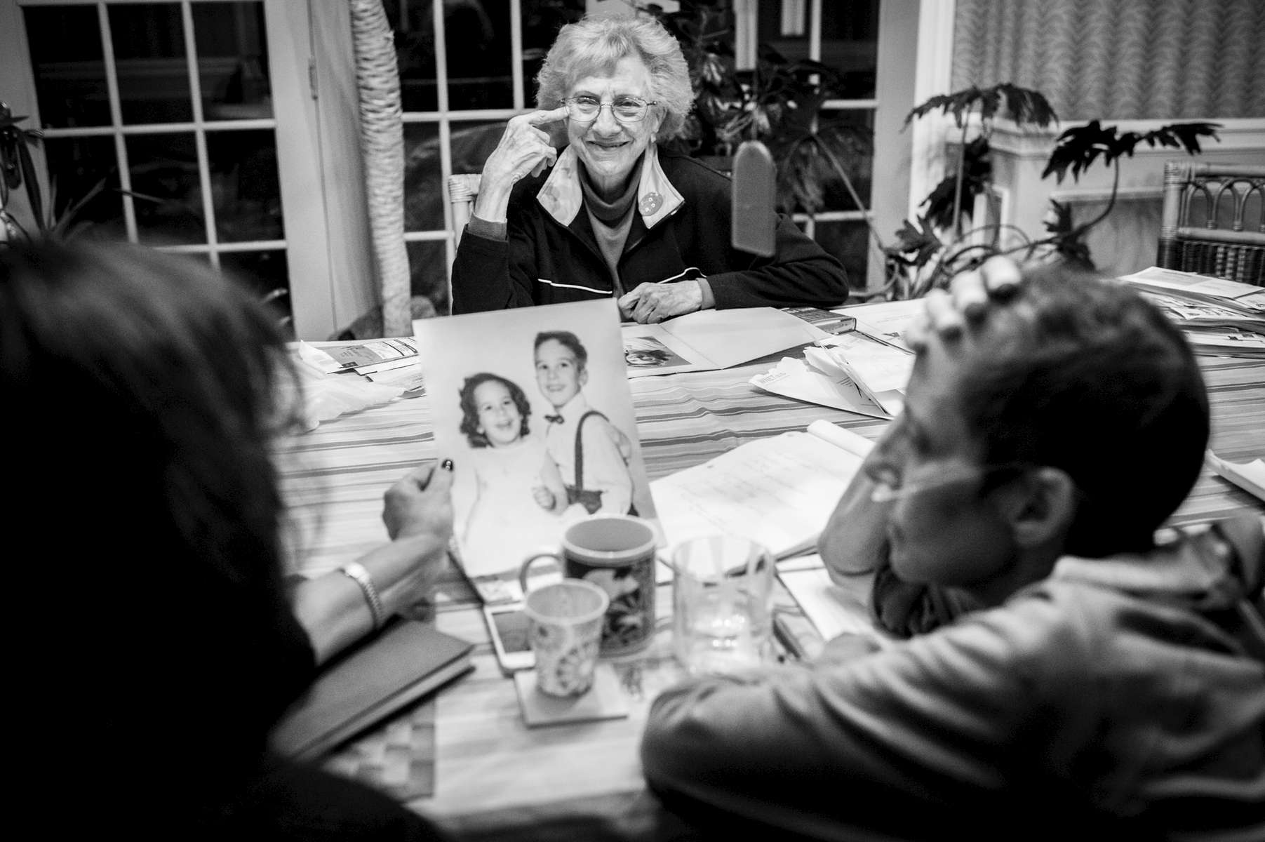 Laurel Borowick sits at her dining room table with best friend Carol Woltz, left, and looks through old photographs that her mother, Marion, has brought over from her childhood. They bring her back to a time and place at the beginning of her life. Chappaqua, NY. December 2014.