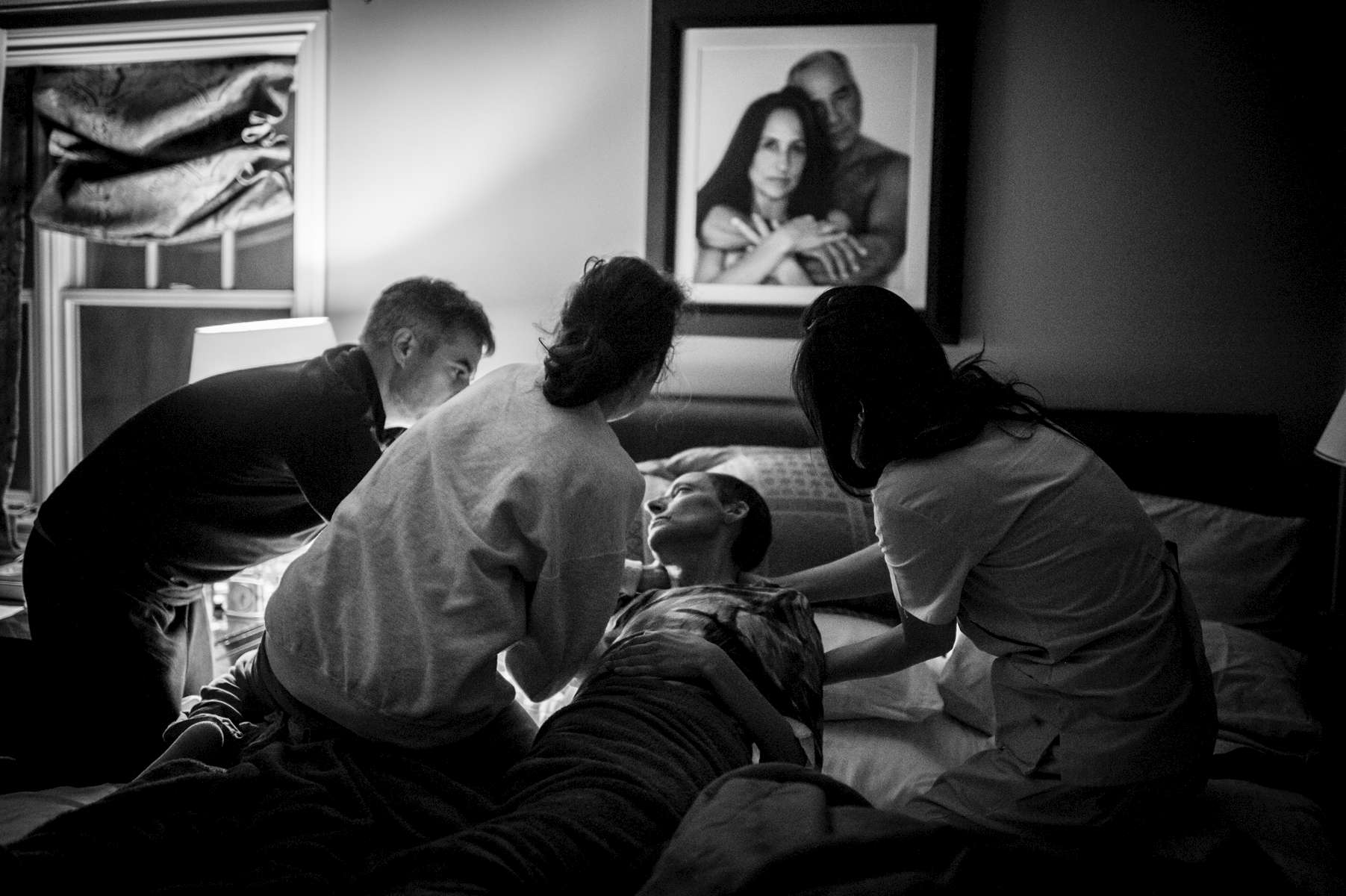After changing her into clean clothing, Paul, her son-in-law, Jessica, her daughter, and Evalina, her caregiver, gently lay her back into her bed. Chappaqua, NY. December 2014.