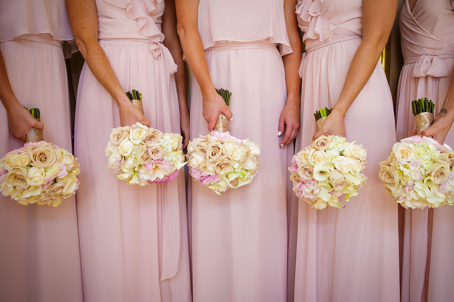 pink-bridesmaid-dresses-against-white-roses
