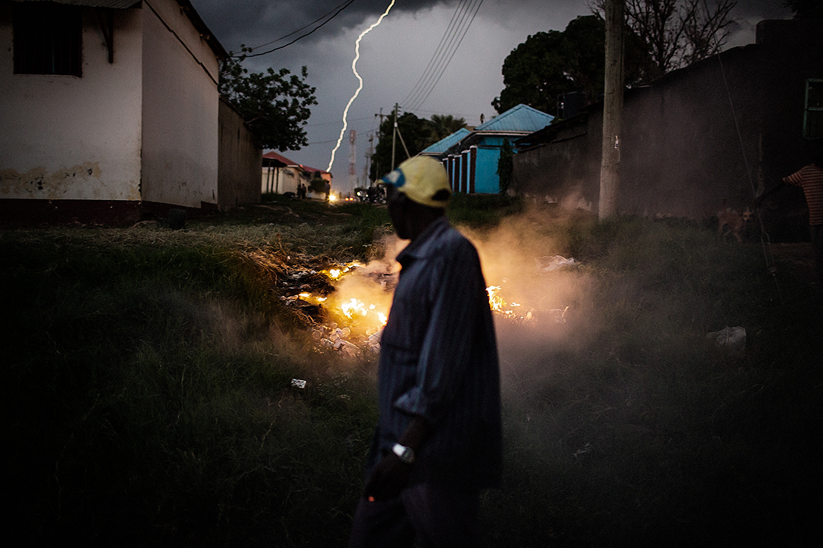 A man walks through Juba past a pile of burning rubbish as a storm begins to erupt over the capital of South Sudan.