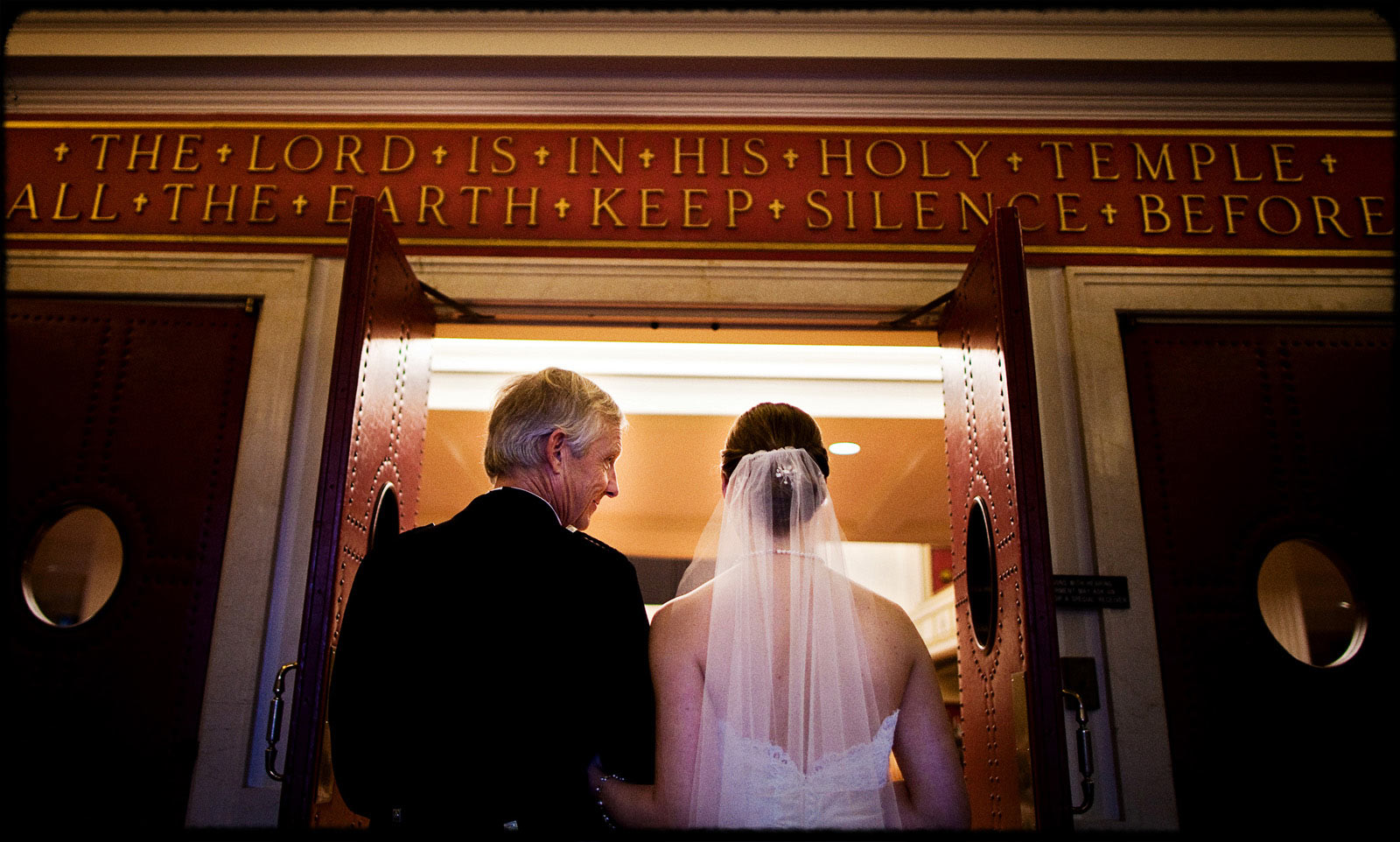 father and daughter walk into first congregational church during wedding ceremony