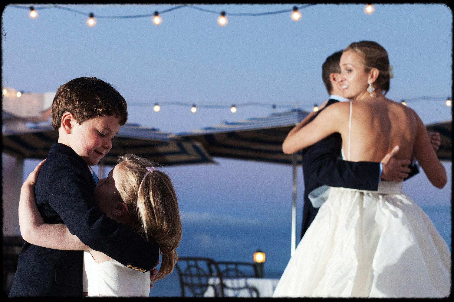 bride and groom watch as kids embrace and dance at wedding