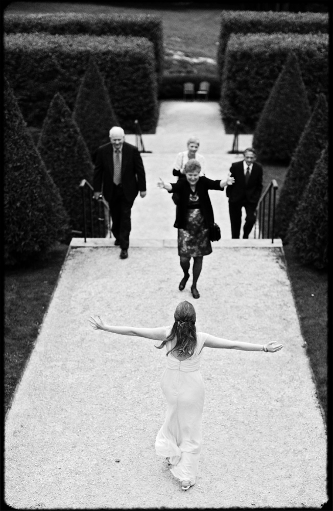 daughter runs toward bride with outstretched arms