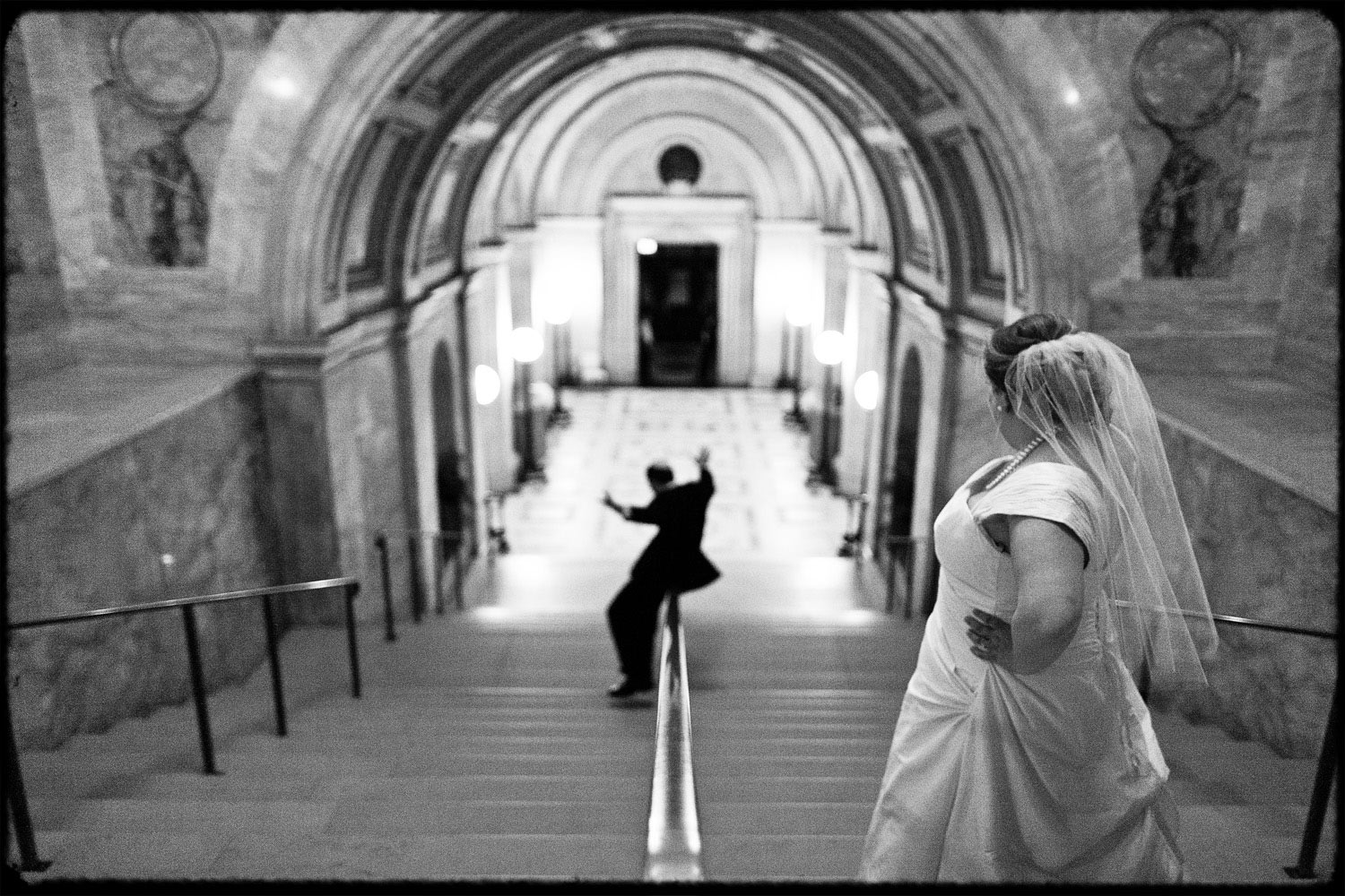 Black and White picture of a groom sliding down the bannister at the Boston Public Library as his bride watches.