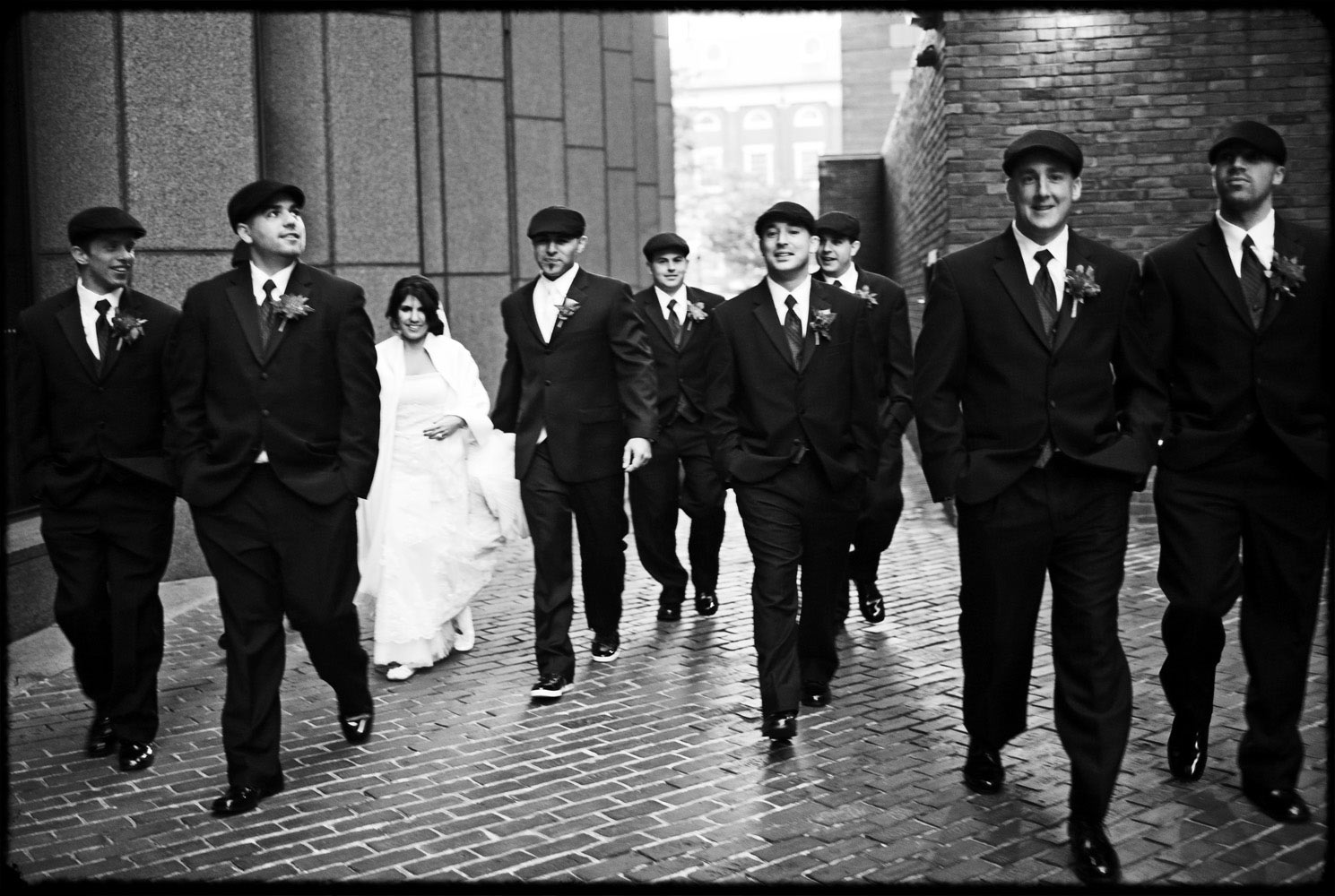 bride walks surrounded by groom and gromsmen