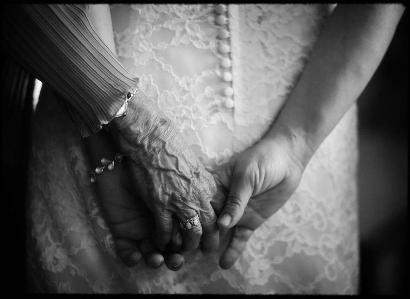grandmother holds bride's hand moments before wedding ceremony