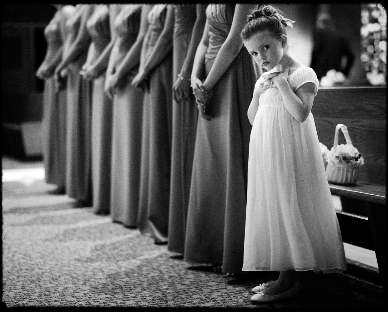 black and white images of a flowergirl staring innocently into the camera in a church during a wedding ceremony