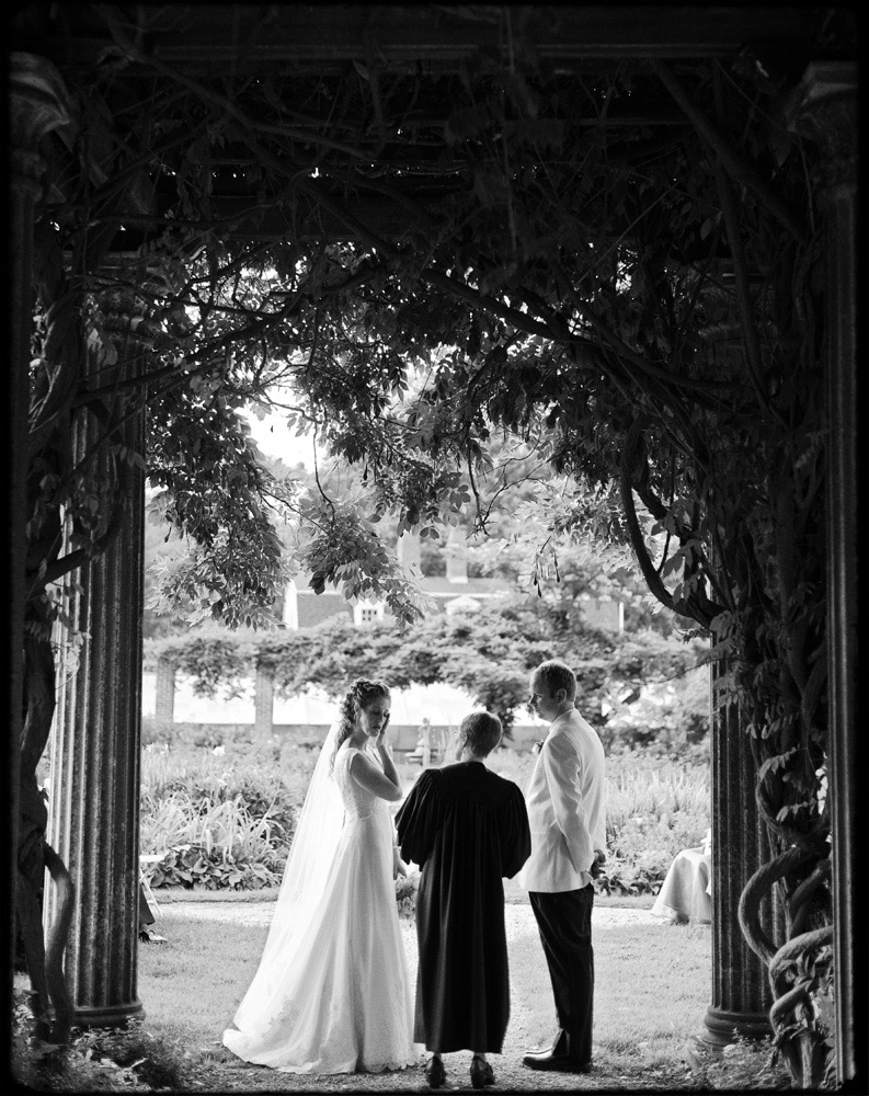 couple standing underneath garden arbor at wedding glen magna