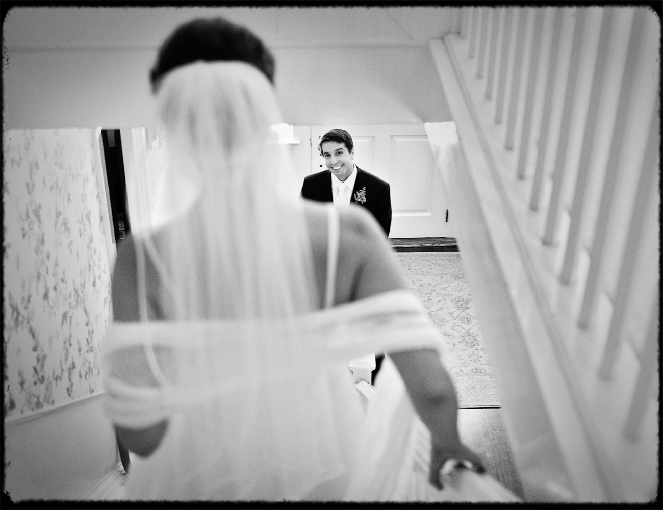 groom sees bride first look on stairway in new hampshire